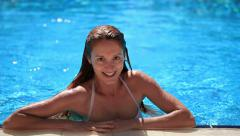 Beautiful slim girl with red hair floats in the pool and smiles. - stock footage
