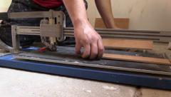 Tiler hands using tile cutter tool on floor. Left side slide Stock Footage