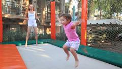 Young mother with her daughter fun jumping on the trampoline. Stock Footage