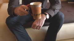 Headless shot, businessman home drinking morning cup of coffee, siting on sofa - stock footage