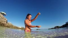 Beautiful girl play with sand and having fun in sea shallow waters Stock Footage