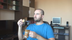 Man in the living room having breakfast, peaceful quiet moments drink cup of tea - stock footage