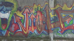 Urban style, groove graffiti wall, young boy listening music on mobile phone Stock Footage