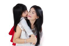child embraces and kiss her mother - stock photo