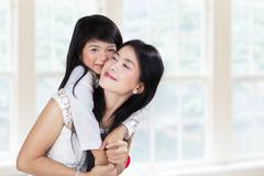 cute girl embrace mother in home - stock photo