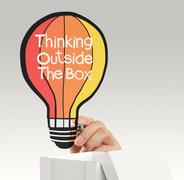 hand drawing balloon lightbulb and thinking outside the box as concept - stock illustration