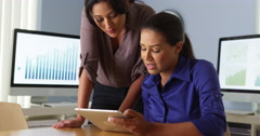 Hispanic business women working with colleague on tablet computer Stock Footage