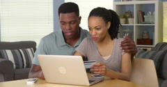 Smiling young black couple using credit card to make online purchase Stock Footage