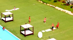 Vacationers at  south beach playing football on artificial turf Stock Footage