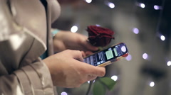 The girl with a rose in hand uses a phone girl writes her boyfriend message. - stock footage