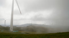 Wind farm with wind turbines making green energy covered with foggy clouds Stock Footage