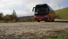 Shuttle bus passing by on the road in a pasture Stock Footage