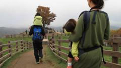 Husband and wife with children walking along wooden fence in a pasture Stock Footage