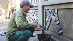 Worker install stone wall surface with cement Stock Footage