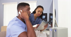 Two African American specialists working together in hospital work station - stock footage