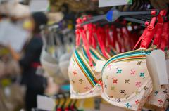 various light color bras with stripes and pictures on stand in store - stock photo
