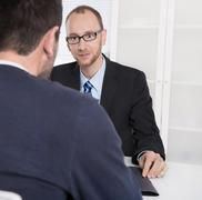 Two business men sitting in the office: meeting or job interview. Kuvituskuvat