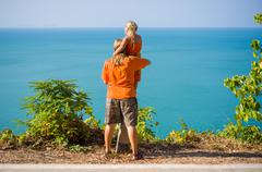 mother and daughter stay on mountain road along tropical island beach and loo - stock photo
