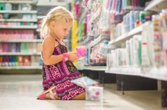 adorable girl select pencil sharpener in stationery department sitting on flo - stock photo