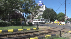 Old streetcar leaves fast station commuting scene in town, tram rails track view Stock Footage