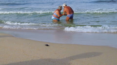 Couple retired to bathe in the sea. Small turtle walking on the beach. Stock Footage