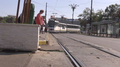 Streetcar move on rails, railway downtown, tram come in station commuters travel Stock Footage
