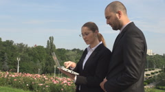 Business finance workers, team working outdoors, man woman on laptop verifying  Stock Footage
