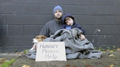 Homeless man and boy beg for change with dog Stock Footage