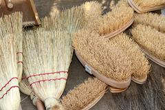 old brooms, brushes and natural material for sale to the market - stock photo