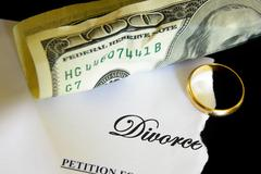 torn divorce decree and cash, with wedding ring - stock photo
