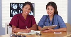 Japanese and Mexican medical doctors sitting at desk Stock Footage