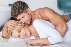Romantic Partners Lying on Bed Fashion Shoot - stock photo