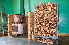 big metal furnace for heating and pile of firewood - stock photo