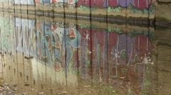 Graffiti wall. Reflection of graffiti in the water. Camera upwards motion. - stock footage