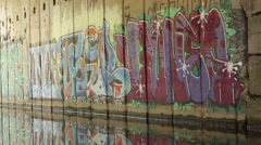 Graffiti  on wall. Reflection of graffiti in the water. Stock Footage