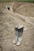 Dirty protective boots at irrigation channel construction site Stock Photos
