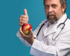 doctor giving apple for healthy eating - stock photo