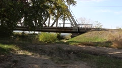 Metal railway bridge with the path. Highway in the background. Stock Footage