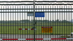 Plane taxis behind security fence Stock Footage
