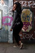 happy black woman posing at wall with vandals - stock photo