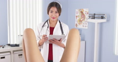 Asian OBGYN examining patient in hospital exam room - stock footage