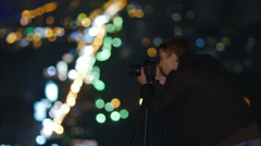 The photographer working at night by picturesque city lights background - stock footage