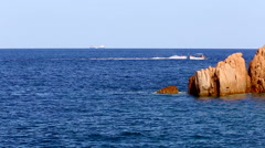 Boat sailing behind a granite rock on a blue sea, in Sardinia, Italy. Stock Footage