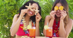 African American and Asian women on vacation goofing around with sea shells - stock footage