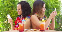 Black and Asian best friends on vacation using mobile phones - stock footage