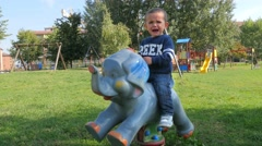 Child on a rocking animal cries because he wants the pacifier Stock Footage