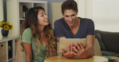 Happy mixed race couple talking on tablet Stock Footage