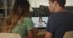 Interracial couple talking with doctor on laptop Stock Footage