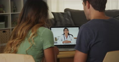Couple talking with a professional doctor online with laptop Stock Footage