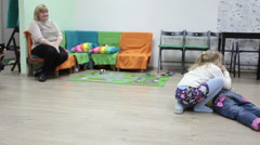 Girl playing on floor when mother looking at them, domestic room Stock Footage